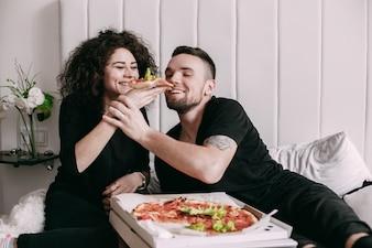 La femme bouclée donne un morceau de pizza à son homme