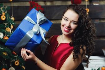 La femme brune bouclée tient la boîte présente bleue