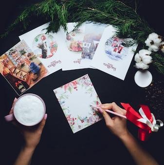 La femme écrit quelque chose sur la carte postale de Noël en tenant une tasse de lait