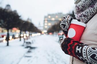 La femme en manches longues tient une tasse de café rouge debout à l'extérieur dans la soirée