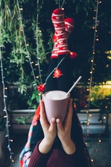 La femme tient dans ses mains une tasse avec du chocolat chaud avant que ses jambes ne s'élèvent