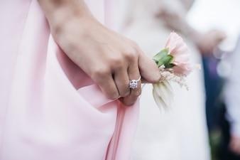 La femme tient une boutonnière rose dans son bras
