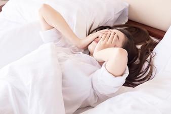 La jeune femme ne peut pas dormir. Sur son lit et sa pensée.