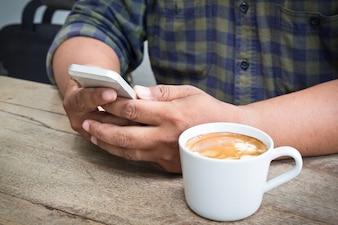 La main de l'homme tient le smartphone et la tasse de café