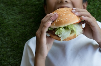 La main du garçon tenant un hamburger