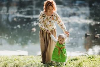La mère avec une fille qui se promène près du lac