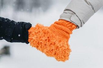 La paire tient la main dans des mitaines orange