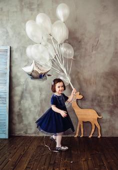 La petite fille garde les ballons dans la pièce