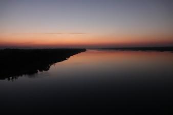 Lac avec rivage au coucher du soleil