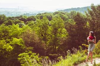 Lady avec bouquet rouge se dresse sur la colline verte