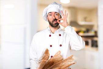 Le jeune boulanger prend du pain et fait un geste de silence dans la cuisine