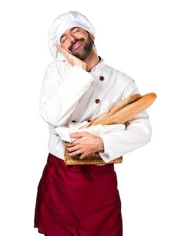 Le jeune boulanger prend du pain et fait un geste de sommeil