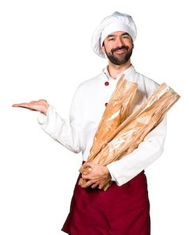 Le jeune boulanger prend du pain et tient quelque chose
