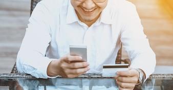 Le jeune homme beau apprécie faire des achats en ligne sur un téléphone mobile avec une carte de crédit.