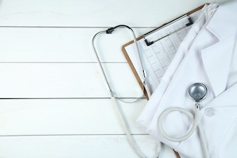 Le stéthoscope, le presse-papiers et l'uniforme du médecin sur le bureau blanc en bois pur