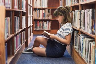 Lecture de fille dans la bibliothèque