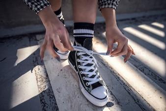 Les détails de la chaussure de femme en laissant ses baskets classiques