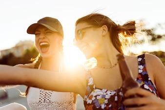 Les filles en souriant avec le soleil au milieu