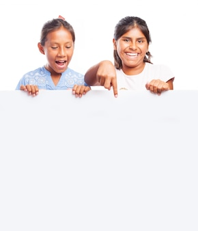 Les filles tenant un panneau blanc et un sourire et pointant