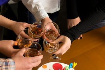 Les gens boivent à la table, clink glasses. À votre santé!