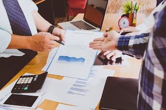 Les gens d'affaires font des remue-méninges au bureau, analysent les rapports financiers et signalent les données financières sur une feuille