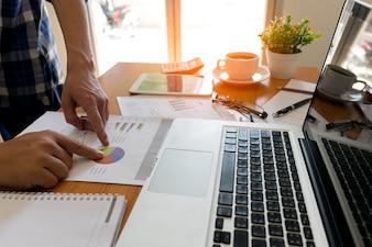 Les gens d'affaires se réconforcent au bureau, ils analysent les rapports financiers et indiquent les données financières sur une feuille