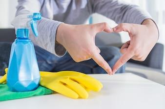 Les gens, le ménage et le concept de ménage - gros plan de la table de nettoyage des mains de l'homme avec du linge et du détergent à la maison