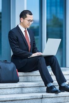 Les hommes d'affaires utilisent des ordinateurs portables à l'entrée d'un immeuble de bureaux