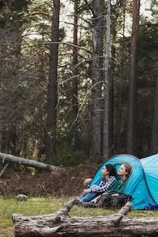 Les jeunes femmes apprécient la nature dans la tente