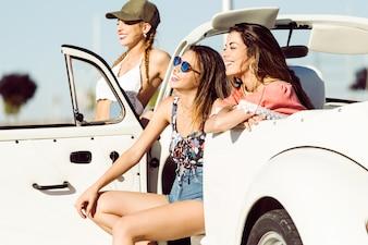 Les jeunes filles en souriant assis dans une voiture
