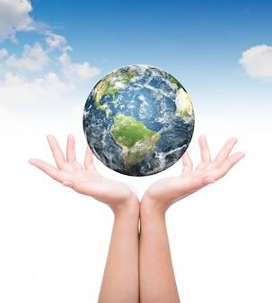 Les mains avec de la planète terre ci-dessus