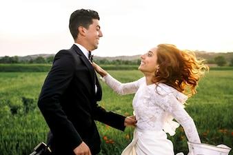 Les nouveaux mariés joyeux sautent sur un terrain vert