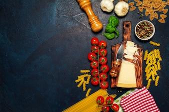 Les tomates avec une planche à découper avec du fromage, des pâtes et des épices