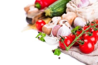 Les tomates, l'ail et les courgettes alignées sur un fond blanc