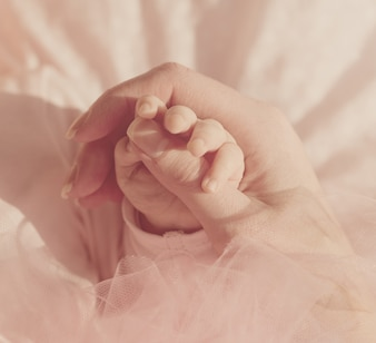 Little Cute Baby Hands in Mother Hand. Fond rose. Pastel.