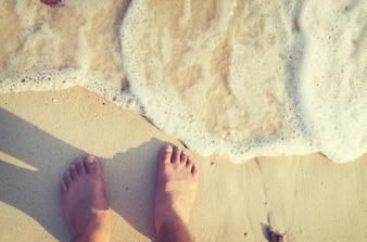 Loisirs en été se détendent sur la plage - Au-dessus du pied de l'homme avec tatouage. rétro filtre effet