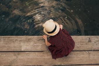 Lone petite fille assise sur la jetée