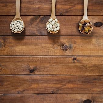 Louches en bois avec des haricots et des noix