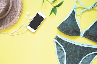 Maillots de bain en couleur verte avec téléphone intelligent et écouteur disposés sur fond jaune
