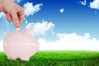 Main avec une pièce de monnaie sur une tirelire rose