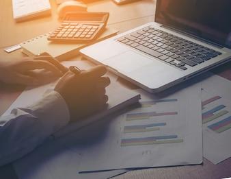 Main d'homme d'affaires travaillant sur le téléphone intelligent et l'ordinateur portable et le diagramme d'information de graphique d'entreprise sur la table en bois avec la réflexion de fenêtre au bureau.