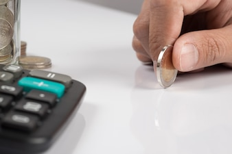 Main humaine tenant une pièce de monnaie et copie, concept de plan d'investissement d'entreprise.
