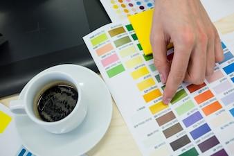 Mains de designer graphique couleur en choisissant des hommes de nuancier