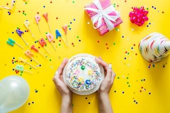 Mains tenant un gâteau d'anniversaire fait maison
