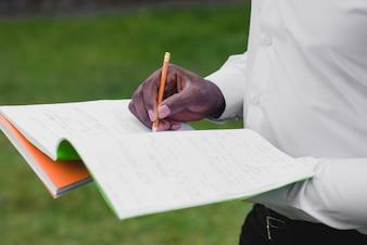 Man holding notebooks writing