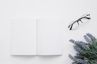 Maquette de couverture de livres avec lunettes et décoration de fleurs