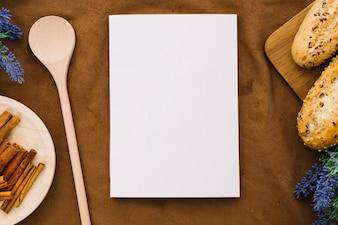 Maquette de livre avec de la cuillère, de la cannelle et du pain