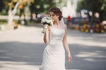 Mariée avec un bouquet dans le parc