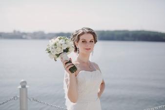 Mariée avec un bouquet dans un lac