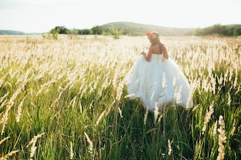 Mariée dans une jolie longue robe posant dans le jardin.